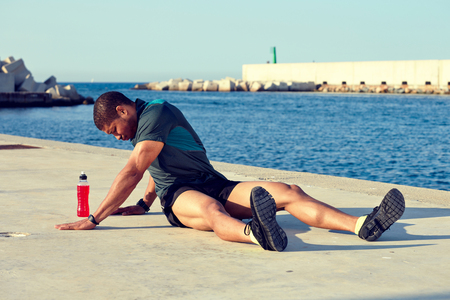muscular build: Male runner doing stretching exercise before began his workout training while sitting on the road with copy space area background, muscular build man playing sports in sunny summer day outdoors,filter Stock Photo