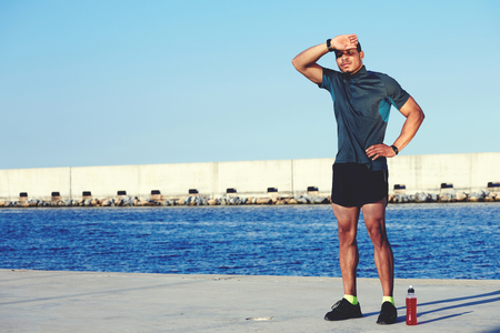 whacked: Weary sportsman rubbing his forehead while resting after workout against sea and sky background with copy space area for your text message or information, sweaty male runner taking break after jog