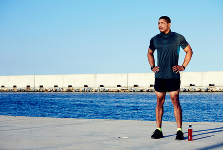 whacked: Strong pumped body man resting after workout in marina port while standing against the sea and sky background with copy space area for your text message or information, male jogger rest after running