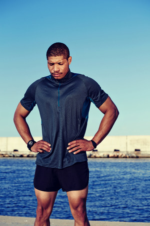strong message: Tired athlete resting after morning run standing on sea and sky background with copy space area for your text message or advertising, strong pumped up sportsman took a break after workout outdoors