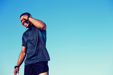 workouts: Happy smiling sportsman having a rest after workouts and standing against blue sky background with copy space area for your text message or advertising, man jogger enjoying  sunny afternoon outdoors Stock Photo