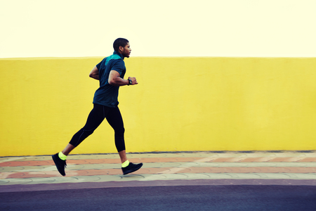 strong message: Strong body male runner working out in the city on yellow copy space wall area for your advertising content or text message,afro american man with muscular pumped shape training at evening jog outside