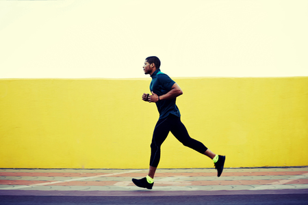 african model: Full length portrait of strong male jogger with muscular body running fast against bright copy space background for your text message or content, pumped man working out while jogging outdoors in city