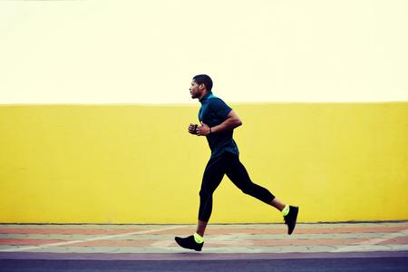 hombres corriendo: Retrato de cuerpo entero de una fuerte Libros masculina, con cuerpo musculoso que se ejecuta rápidamente contra el fondo brillante copia espacio para su mensaje de texto o contenido, el hombre bombeado que se resuelve, salir a correr al aire libre en la ciudad
