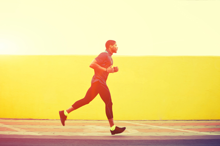 out of body: Full length portrait of afro american runner with muscular body in tracksuit jogging against yellow wall with copy space area for your text message or content, young male jogger working out outdoors Stock Photo