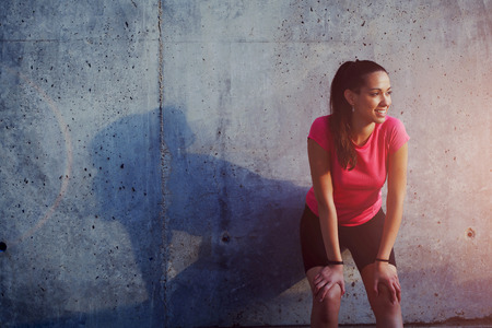 Half length portrait of young smiling female resting after an active fitness training while standing on a background of gray wall with copy space area for your text message or concept, satisfied fit woman resting after an active fitness training Standard-Bild