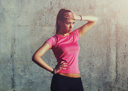 intensive: Attractive sportswomen standing on a background of gray wall after intensive fitness training Stock Photo