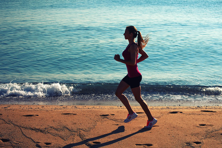 purposeful: Full length portrait of purposeful woman runner with beautiful figure doing daily evening run on the ocean beach, young female athlete with hair tied up in a ponytail engaged in active sports against the sea