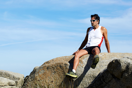 discharge time: Adult male athlete resting after workout outdoors sitting on a stone rock against blue sky  background with copy space area for your text message or content, sportsman listening to music in headphones