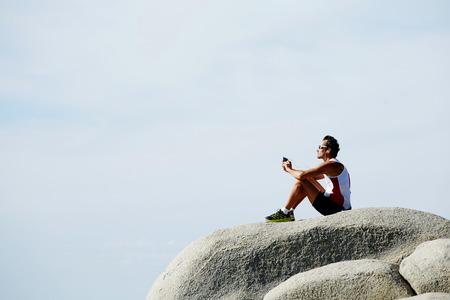 tomando refresco: corredor masculino que escucha la m�sica en los auriculares mientras se est� sentado en el acantilado de roca contra el cielo de fondo copia espacio para su mensaje de texto o la publicidad, el basculador madura cansada de descanso despu�s de ejercicios de desplazamiento al aire libre Foto de archivo