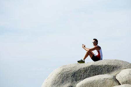 Atleet man zittend op een stenen rots luisteren naar muziek in de koptelefoon tijdens de rust na de training, sportman geniet landschap tegen hemel kopie ruimte achtergrond voor uw tekstbericht of informatie