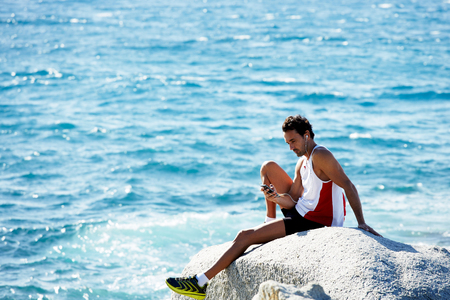 tomando refresco: Mature male runner sitting on sea rock cliff enjoying outdoors with feeling of freedom, athlete man resting after workout in sunny day against copy space area for your text message or advertising Foto de archivo
