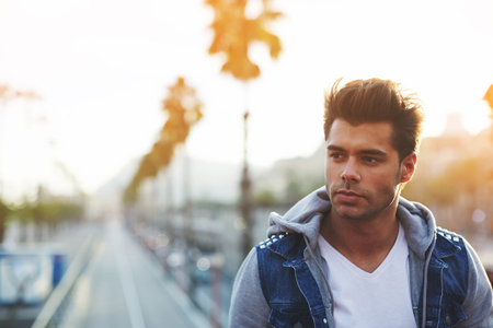 brunnet: Handsome thoughtful man looking away while standing against road and sky background with copy space area for your text message or content, attractive male posing for camera on the street outdoors Stock Photo