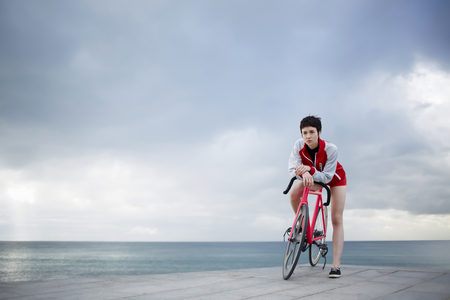 proffessional: Young stylish female cyclist leaning on her light weight fixed gear bicycle while standing against copy space dramatic sky on seashore, sporty woman actively enjoying weekend strolling on her bike Stock Photo