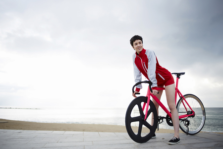 active wear: Full length portrait of young sporty woman dressed in active wear have a minute break after ride on her sport fixed gear bicycle at coastline outdoors, young woman at seashore enjoying recreation time Stock Photo