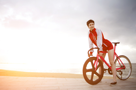 active wear: Attractive female dressed in flamboyant active wear rest after ride on her sport fixed gear bicycle, female enjoying weekend stroll on rental bike while standing against dramatic sky witn copy cpace