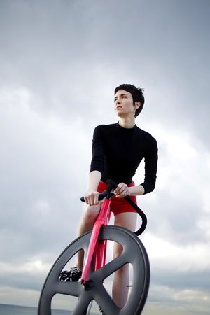 proffessional: Full length portrait of stylish young hipster girl standing on the beach with her fixed gear bicycle at seashore against copy space cloudy sky,beautiful woman resting after ride on sport bike outdoors Stock Photo