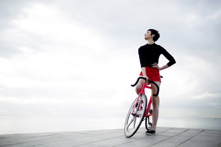active wear: Full length portrait of stylish young woman dressed in flamboyant active wear standing with her modern sports fixed gear bicycle against copy space area cloudy sky,female hipster enjoying calm scenery
