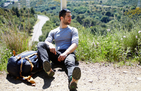 weary: Portrait of a weary traveler taking break after active walk in mountains, male hiker enjoying landscape scenery while sitting on top hill with backpack and looks aside, tourist resting after hike way
