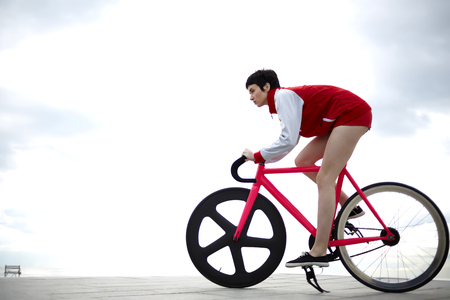 proffessional: Stylish hipster girl dressed in a red sport jacket and shorts riding on her weight fixed gear bicycle against of cloudy sky background with copy space area for your text message or advertising content Stock Photo