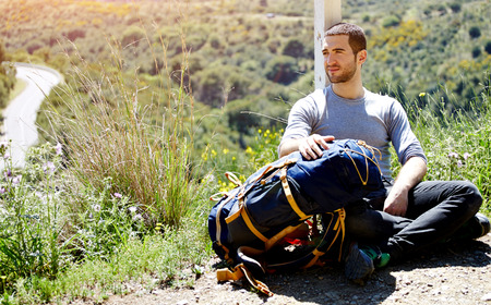 people relaxing: Tired hiker with backpack resting after active walk in mountains, traveler man enjoying scenery landscape view on top of hill with copy space area background for your text message or advertise content Stock Photo