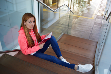 prettiness: Attractive young university student preparing for the exam while reading her notepad at campus interior, stylish hipster girl resting after classes sitting on the stairs in the hallway of university Stock Photo