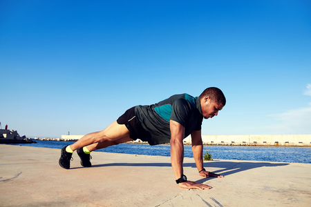 strong message: Runner man with a muscular body doing push-ups on concrete pier against blue sky background with copy space area for your text message or content, strong male engaged in physical activity outdoors Stock Photo