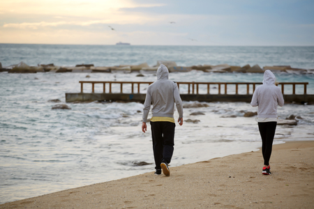 activewear: Back view of a young runner men and woman resting after an morning jogging, sport couple taking break after workout while they walking on beach with copy space area for your text message or content