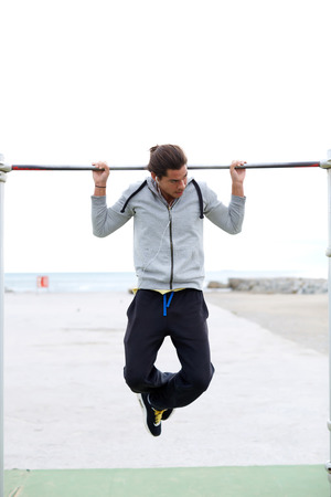 pull up: Young strong athlete doing pull up exercise outdoors at street gym and listening to music in headphones, male runner working out on horizontal bar in cloudy day, sportsman do physical exercises