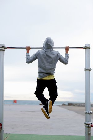 Back view of a male runner doing pull ups on the horizontal bar while training at evening outdoors, strong athlete in tracksuit doing exercise at street gym apparatus, young sportsmen playing sports
