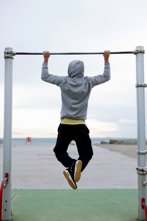 active wear: Back view portrait of  young bodybuilder in active wear doing pull ups on the horizontal bar outdoors, strong athlete doing exercise in a cloudy morning outside, fit man working out at street gym Stock Photo