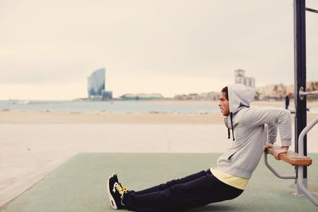 personas escuchando: Vista lateral retrato de hombre fuerte que hace ejercicios de los músculos en el aparato del entrenamiento al aire libre, el hombre en forma bombas bíceps barra horizontal en la orilla del mar, deportista a la actividad física en la mañana fría nublado, filtro Foto de archivo