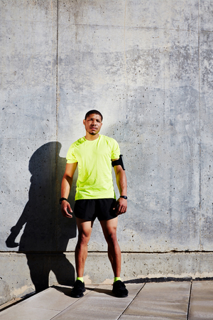 strong message: Full length portrait of strong man jogger took break after workout while standing against cement wall background with copy space area for your text message information, athlete resting after running