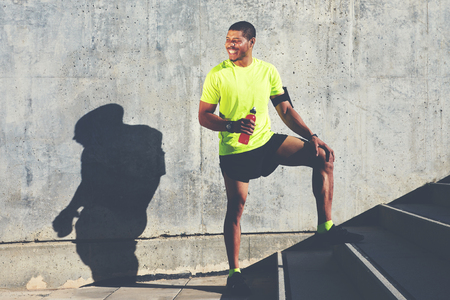 Smiling male runner in bright t-shirt holding bottle of energy drink while standing against cement wall background with copy space area for your advertising, happy afro american athlete having a rest Stock Photo