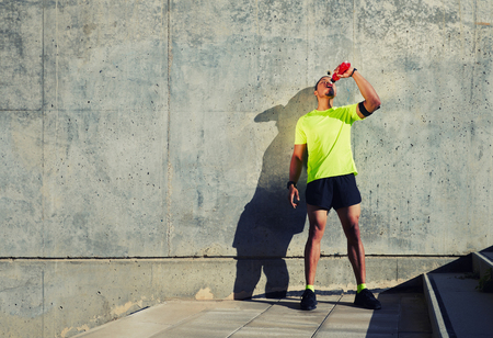 sweaty: Full length portrait of sweaty man runner refreshing with energy drink water after jogging against cement wall background with copy space area for your text message or content,sportsman having a rest Stock Photo