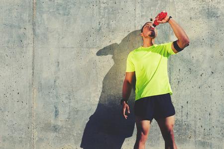 deportista cansada joven con refrescante bebida energética mientras está de pie contra el fondo pared de cemento con área de espacio de la copia para su mensaje de texto o contenido, corredor de descanso después de hacer ejercicio al aire libre masculino