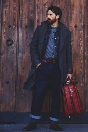 area sexy: Confident modern tourist standing with vintage suitcase on wooden door background  with copy space for text message or advertising, elegant fashionable hipster man dressed in coat waiting for someone Stock Photo