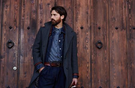 Handsome zuversichtlich reifen Mann mit Bart steht auf hölzernen braunen Hintergrund mit Kopie Platz für Ihre SMS-Nachricht oder Werbung, modische reiche männlich gekleidet in teure Kleidung posiert im Freien
