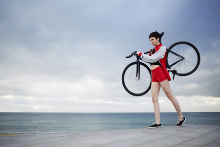proffessional: Full length portrait of professional female rider dressed in red sport jacket and shorts holding her light weight fixed gear bicycle while standing on concrete pier seashore with copy space cloudy sky