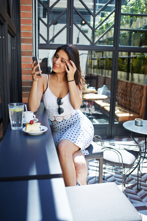 area sexy: Elegant business woman with perfect curvy figure sitting in a restaurant while using her smartphone as a mirror for make up, beautiful Brazilian female sitting at coffee shop and waiting for someone Stock Photo