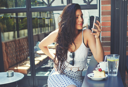 sidewalk talk: Young well dressed woman with a perfect figure looking to her smartphone screen while breakfast in restaurant terrace, attractive latin female browsing internet on her touchscreen phone at coffee shop Stock Photo