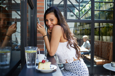 area sexy: Laughing female brunette with long beautiful hair dressed in a trendy clothes chatting on her smartphone, young woman having breakfast in open air cafe while connecting to wireless via mobile phone Stock Photo