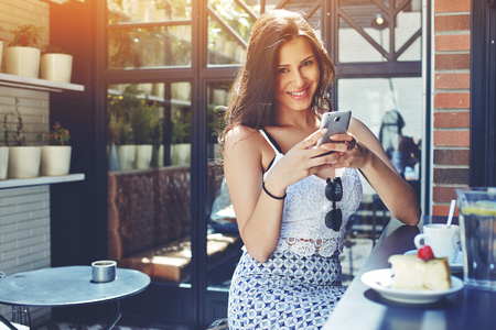 sidewalk talk: Young attractive appearance happy female using the mobile phone network while breakfast in coffee shop, beautiful Brazilian woman smiling brightly holding smartphone with copy space area on the side Stock Photo