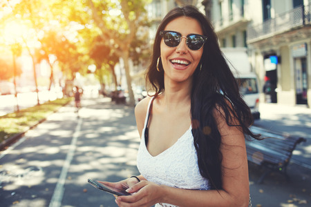 Happy Latin woman in summer sun glasses smiling brightly while holding smartphone strolling outdoors in the city at sunny day, female person using mobile standing with composition copy space on a side Stock Photo