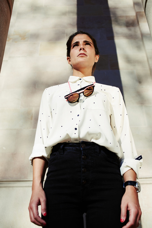 afield: Low view portrair of stylish young woman in trendy clothes and classy sunglasses hanging on the neck looking focused afield standing against antique building outdoors, hipster girl posing for camera Stock Photo