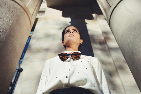 conceived: Low view portrair of a young beautiful woman with stylish clothes and classy modern sunglasses standing near a large building with conceived serious face looking afield, female posing for the camera
