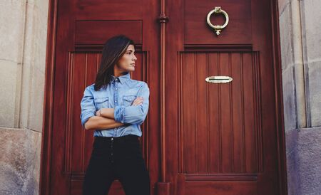 Young hipster girl posing for the camera on a background of brown wooden door with copy space for your text message or content,confident stylish woman looks to the side while standing in urban setting 版權商用圖片