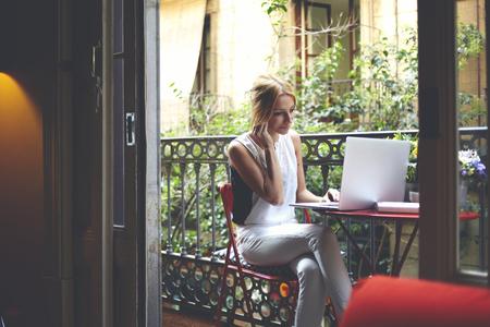 usando computadora: el éxito del trabajo profesional independiente chica joven en su ordenador portátil mientras está sentado en el balcón casa, inteligente y atractiva estudiante de sexo femenino que usa el ordenador de navegación en Internet y escuchar música con auriculares Foto de archivo