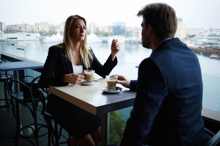 Pár sikeres befolyásos vezetők, amelynek ülésén vita közben iszik kávézó, üzletemberek beszélnek egymással alatt kávészünet a modern luxus helyen, tengerre néző Marina Port