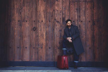 Portrait des stilvollen bärtigen zuversichtlich Mann mit Vintage-Koffer mit Kopie Platz auf einem hölzernen Wand Hintergrund stehen für Ihre Textnachricht oder Inhalt, männlichen Modell mit zuversichtlichen Blick posiert im Freien